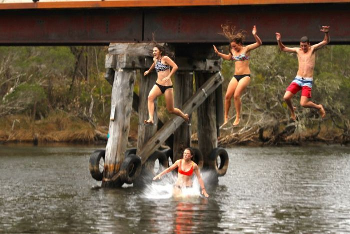 Jumping off the old railway bridge at the river mouth caravan park in Denmark WA